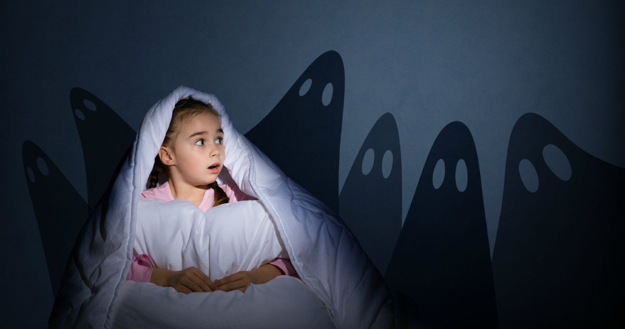young girl having nightmares in bed